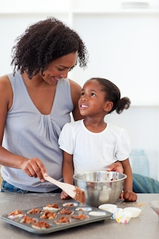 Gelukkige moeder die haar dochter kokende koekjes helpen