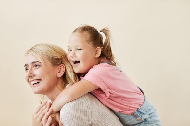 Gelukkige moeder die haar dochter met het syndroom van down op haar rug tegen de witte achtergrond berijdt