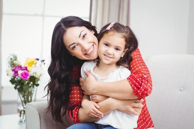 Gelukkige moeder die haar dochter thuis omhelst