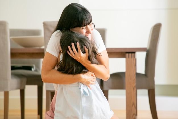 Gelukkige moeder die haar mooie dochter met beide handen omhelst.