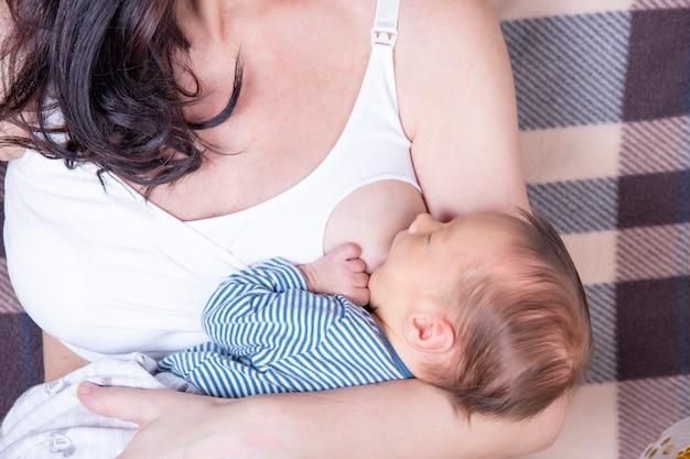 Gelukkige moeder die haar pasgeboren baby de borst geeft