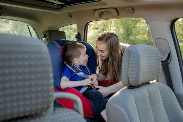 Gelukkige moeder die haar zoon in een babyzitje bekijkt. jong wijfje dat jong geitje voorbereidt voor een reis. veiligheid rijden concept.
