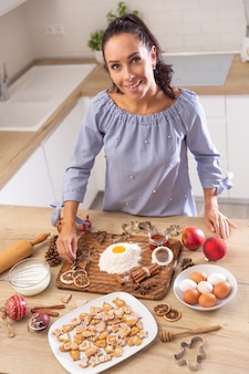 Gelukkige moeder die kerstkoekjes en peperkoeken bakt. ze gebruikt eieren, bloem, kaneel en gedroogde sinaasappelen als decoratie.