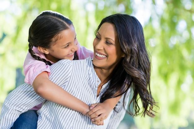 Gelukkige moeder die op de rug rit geeft aan haar dochter