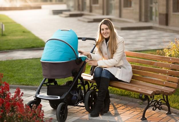 Gelukkige moeder die op een bank zit en naar haar baby in de kinderwagen kijkt