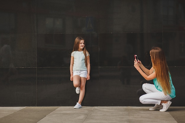 Gelukkige moeder die portretkind op smartphone neemt