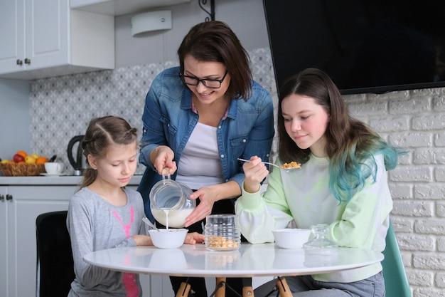 Gelukkige moeder die voor dochters in keuken zorgt