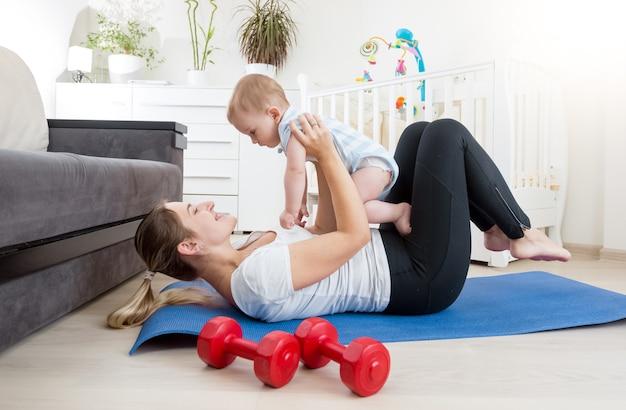 Gelukkige moeder die yoga doet met haar babyjongen op de vloer in de woonkamer