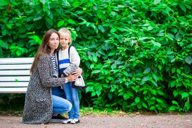 Gelukkige moeder en aanbiddelijk meisje die van warm weer genieten bij mooi park