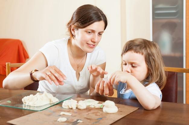 Gelukkige moeder en baby beeldhouwen uit plasticine of deeg in huis