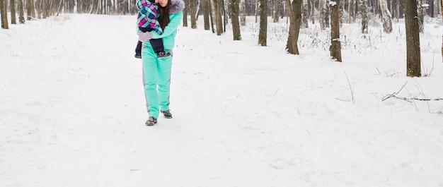 Gelukkige moeder en baby in de winterpark. familie buitenshuis. vrolijke mama met haar kind.