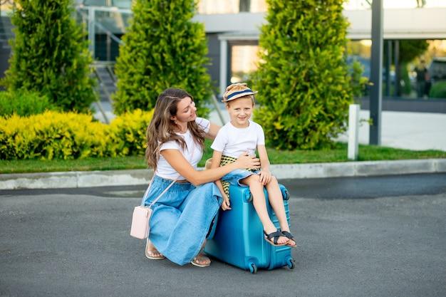 Gelukkige moeder en baby zitten op een blauwe koffer voor de luchthaven en gaan op vakantie of reizen naar de luchthaven
