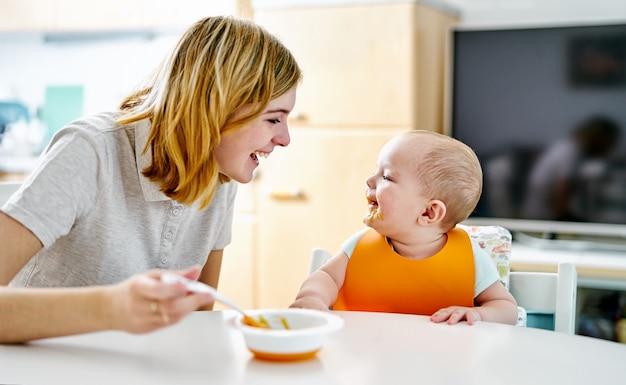 Gelukkige moeder en babyjongen die tijdens het eten glimlachen