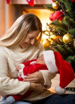 Gelukkige moeder en babyjongen in kerstmankostuum zitten in de woonkamer