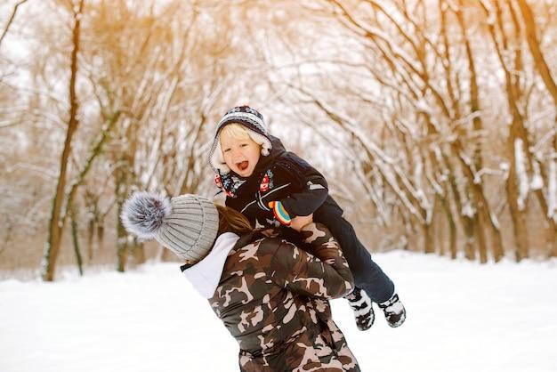 Gelukkige moeder en babyzoon die samen pret hebben bij de winterpark. leuke familie spelen met sneeuw en buiten wandelen. gelukkige en gezonde jeugd
