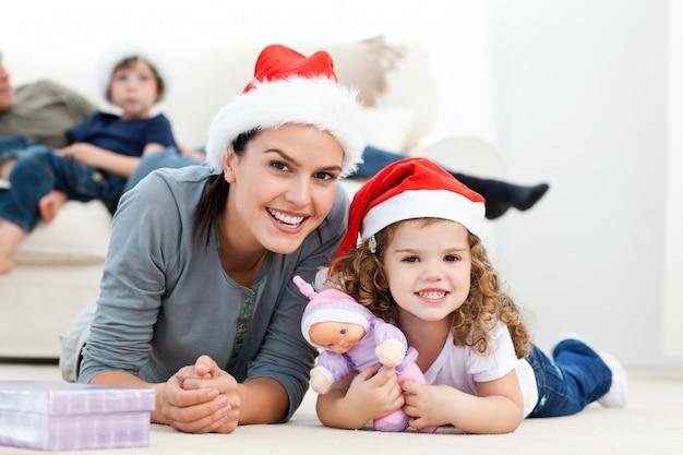 Gelukkige moeder en daugher bij kerstmis die op de vloer liggen