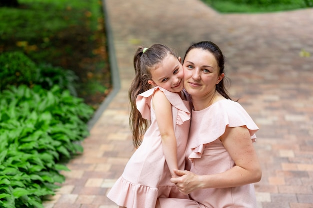 Gelukkige moeder en dochter 5-6 jaar lopen in het park in de zomer, moeder knuffelt haar dochter, het concept van een gelukkig gezin, de relatie van moeder en kind, moederdag