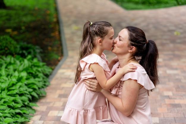 Gelukkige moeder en dochter 5-6 jaar lopen in het park in de zomer, moeder kust haar dochter, het concept van een gelukkig gezin, de relatie tussen moeder en kind
