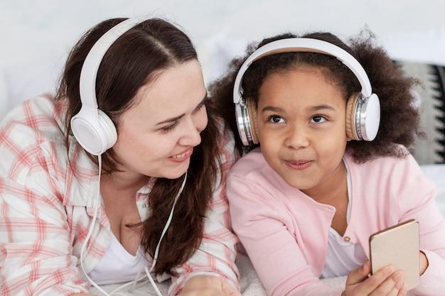Gelukkige moeder en dochter die aan muziek luisteren