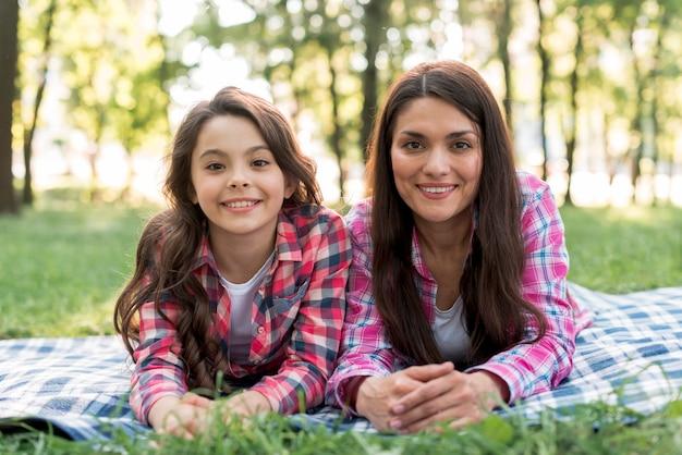 Gelukkige moeder en dochter die camera bekijken die op deken over grasrijk land in park liggen
