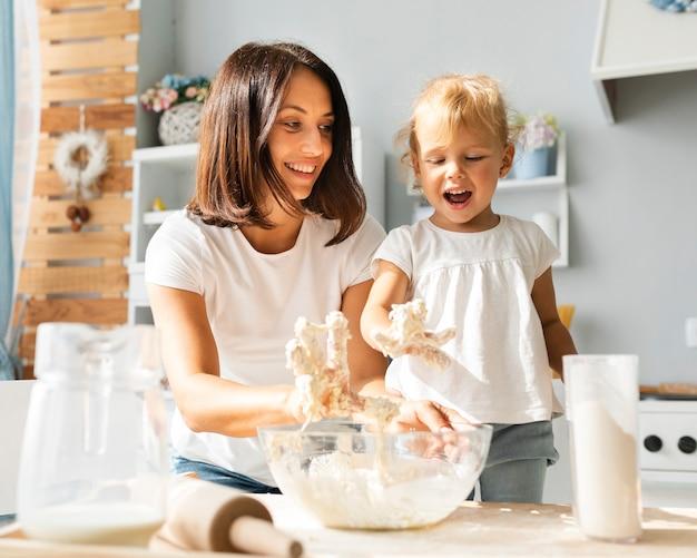 Gelukkige moeder en dochter die deeg voorbereiden