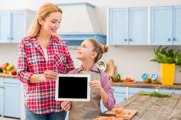 Gelukkige moeder en dochter die digitale tablet houden die ter beschikking elkaar bekijken