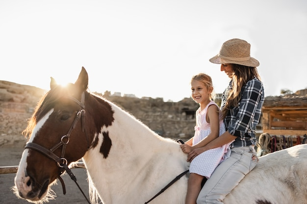 Gelukkige moeder en dochter die een paard berijden bij zonsondergang