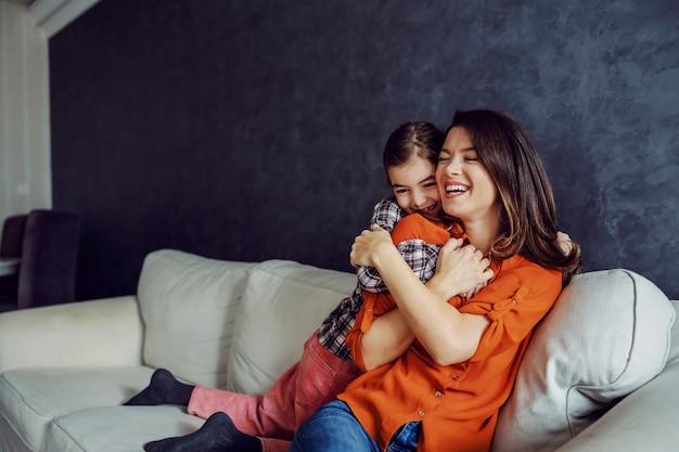 Gelukkige moeder en dochter die elkaar knuffelen en veel liefde duwen.