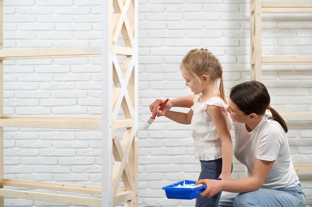 Gelukkige moeder en dochter die houten planken schilderen