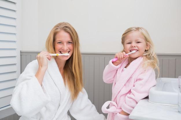 Gelukkige moeder en dochter die hun tanden borstelen