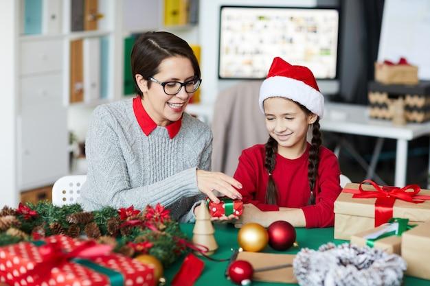 Gelukkige moeder en dochter die kerstcadeaus verpakken