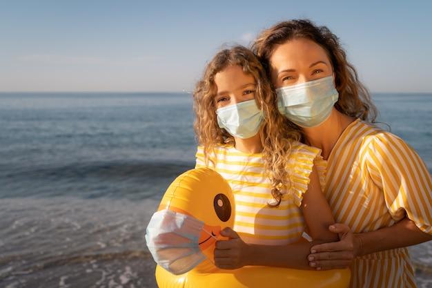 Gelukkige moeder en dochter die medisch masker dragen openlucht tegen blauwe hemel.