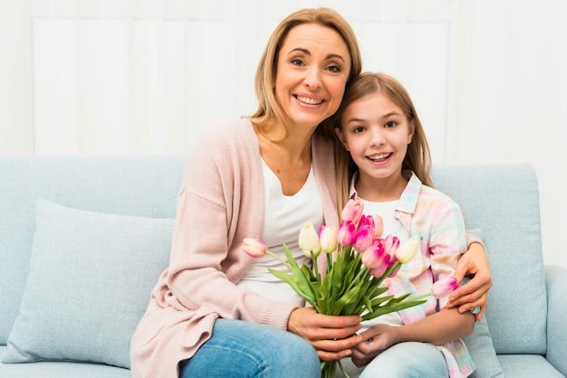 Gelukkige moeder en dochter die met tulpen koesteren