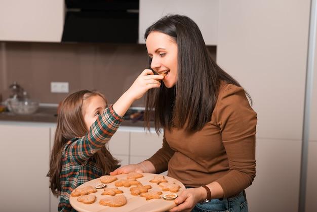 Gelukkige moeder en dochter die net gebakken koekjes in keuken proeven