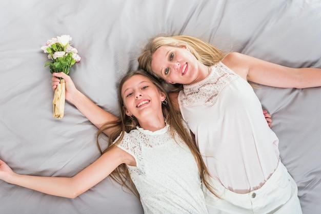 Gelukkige moeder en dochter die op bed met bloemen liggen
