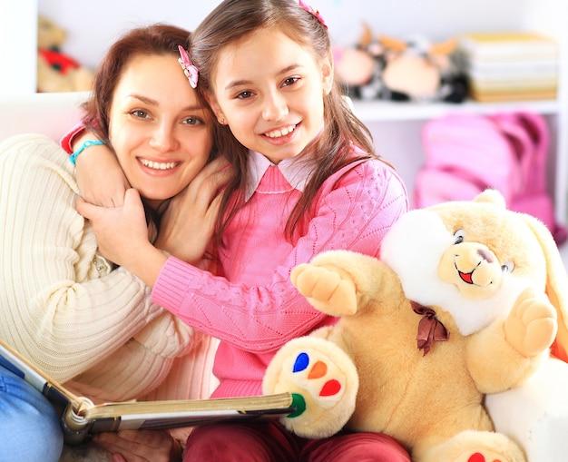 Gelukkige moeder en dochter die samen een boek lezen