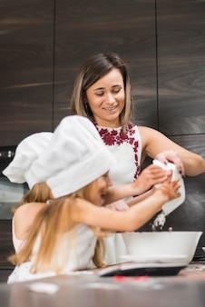 Gelukkige moeder en dochter die voedsel in keuken voorbereiden