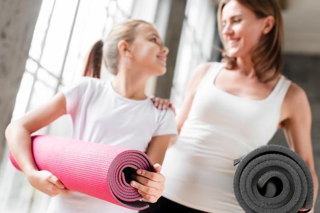 Gelukkige moeder en dochter die yogamatten houden