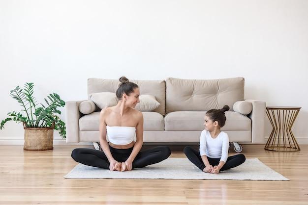 Gelukkige moeder en dochter gaan sporten beoefenen van yoga thuis uitrekken
