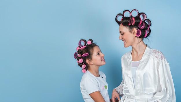 Gelukkige moeder en dochter in krulspelden