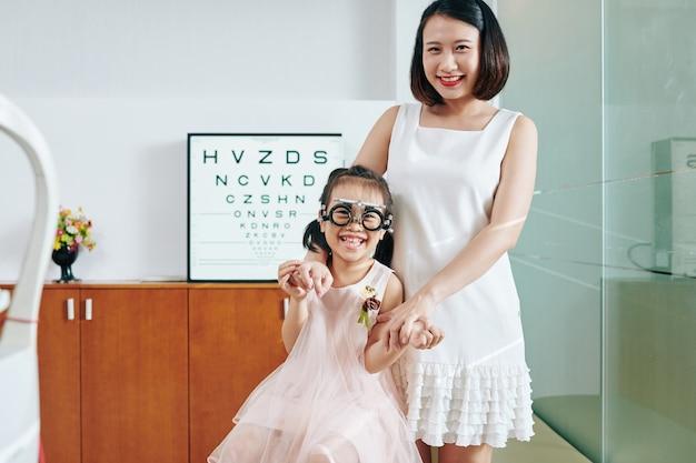 Gelukkige moeder en dochter in proefkaders in bureau van pediatrische oogarts