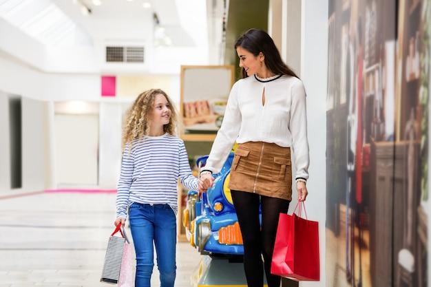 Gelukkige moeder en dochter in winkelcentrum