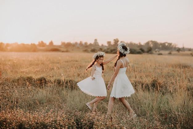 Gelukkige moeder en dochter in witte jurken draaien en hebben vreugde en geluk in de zomer