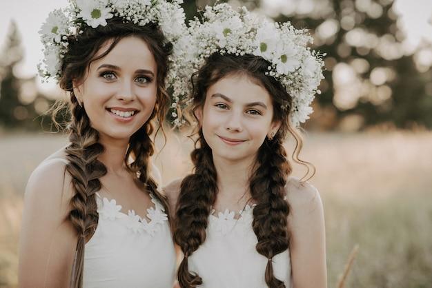 Gelukkige moeder en dochter in witte jurken met bloemenkransen en boho-stijl vlechten in de zomer in een veld