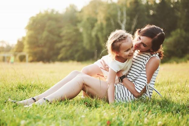 Gelukkige moeder en dochter knuffelen in een park in de zon op een heldere zomer van kruiden.
