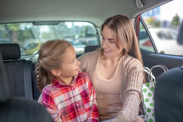 'gelukkige moeder en dochter knuffelen op de achterbank van de auto
