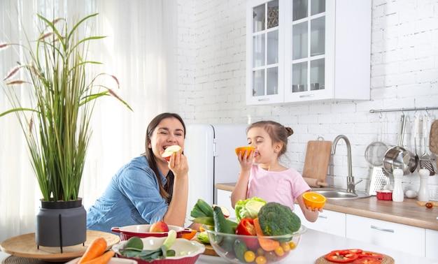 Gelukkige moeder en dochter koken graag in een lichte, ruime keuken