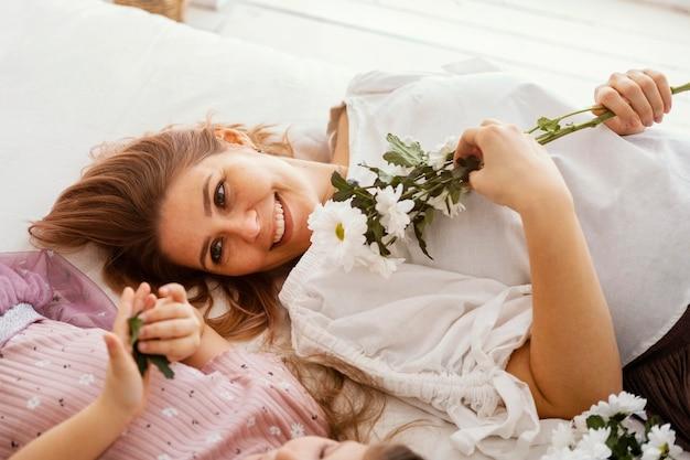 Gelukkige moeder en dochter met boeket van delicate lentebloemen