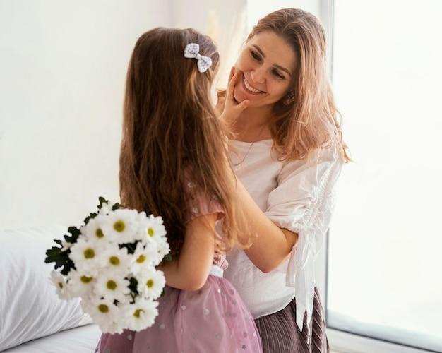 Gelukkige moeder en dochter met boeket van lentebloemen