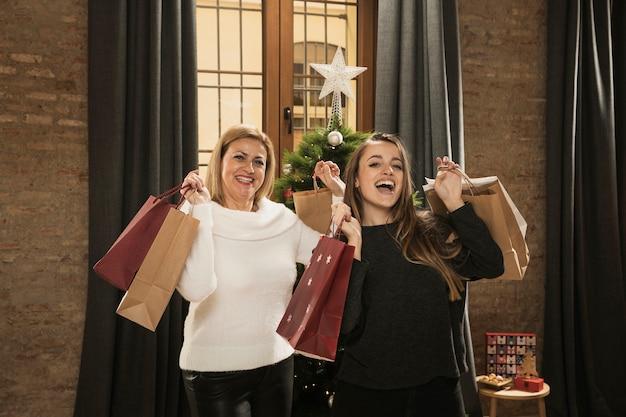 Gelukkige moeder en dochter met boodschappentassen